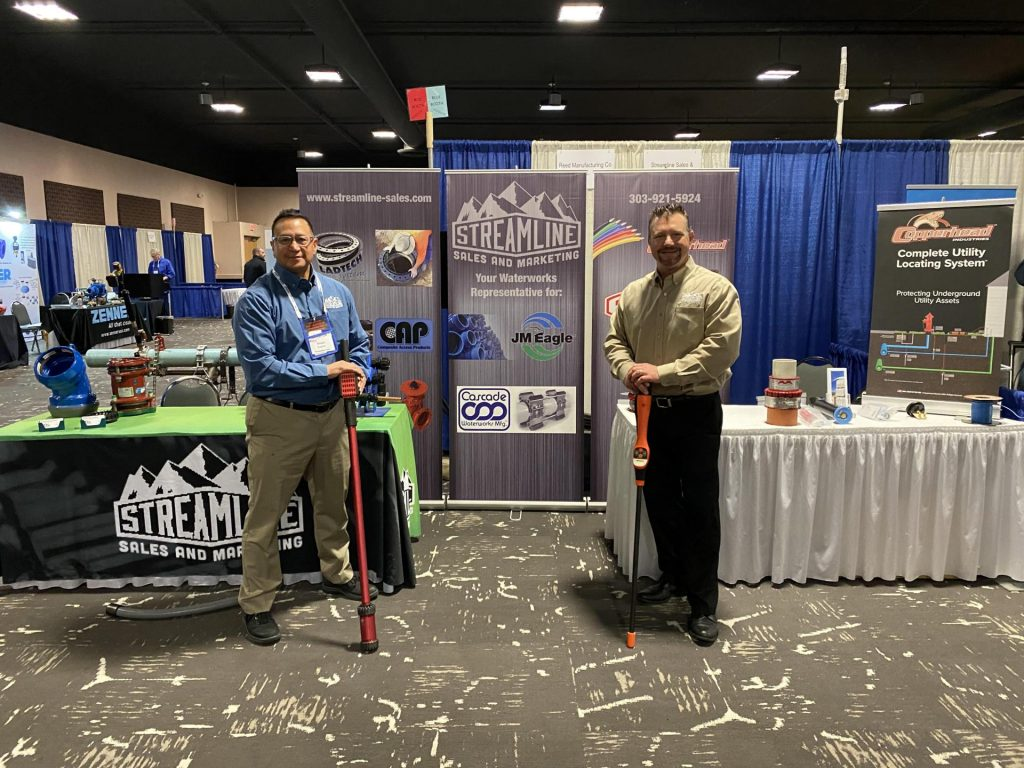 Jeremy and Frank posing in front of their display booth at a conference